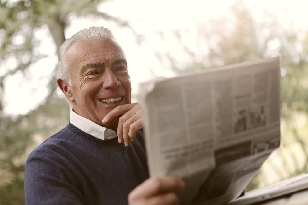 Man reads newspaper.