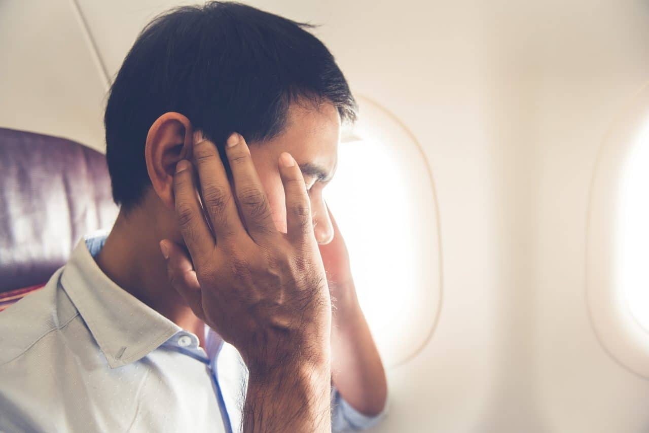 Man experiencing ear pressure on a plane.